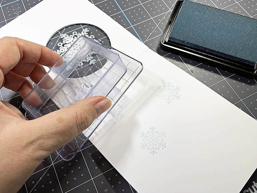 Stamping the snowflakes on the inside of the card.