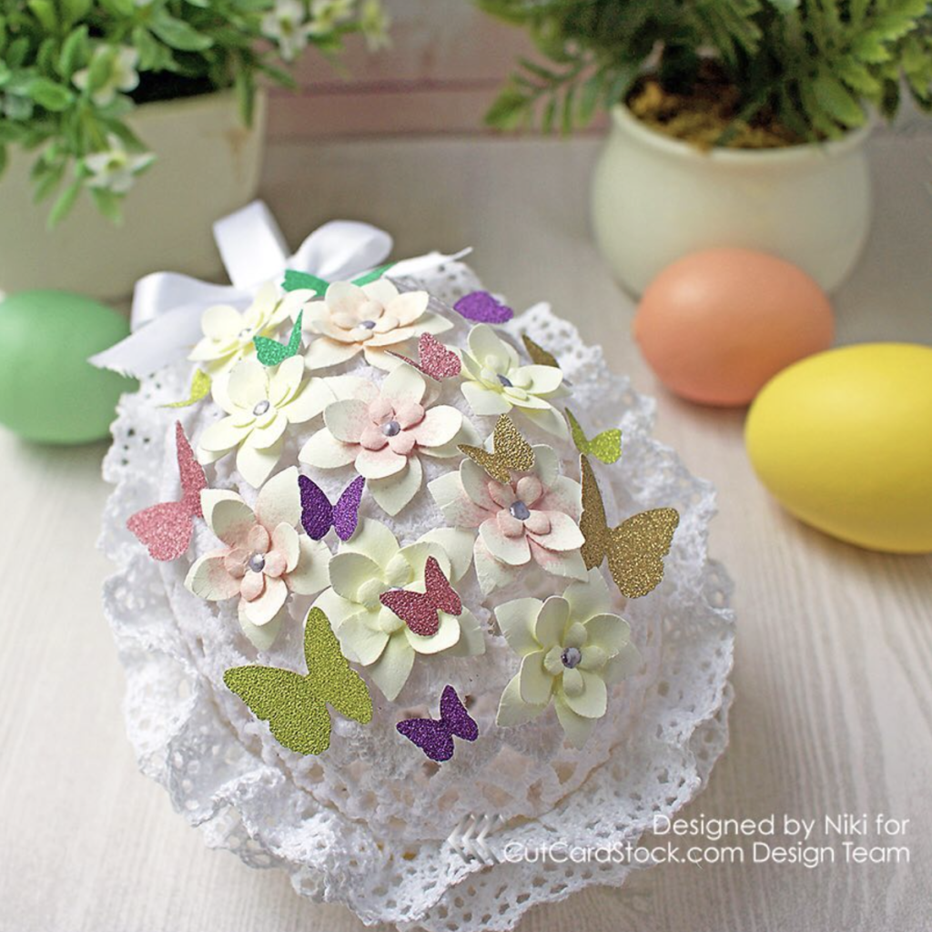 Handmade lace egg decorated with glitter shapes, from Cardstoq. Embrace your creativity!